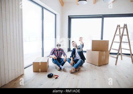 A man with VR goggles and his senior father furnishing new house, a new home concept. - Stock Image
