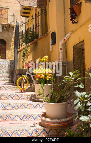 Italy Sicily Agrigento old town steep narrow streets scene stone painted steps stairs plants planters cactus cacti houses balconies drainpipe - Stock Image