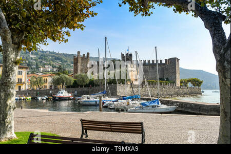 TORRI DEL BENACO, LAKE GARDA, ITALY - SEPTEMBER 2018: Scenic landscape view of the small harbour in Torri del Benaco  on Lake Garda, framed by trees - Stock Image