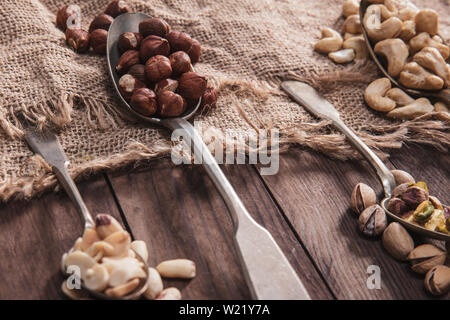 Close-up on different kinds of nuts on old spoons and composition from old wood and material - Stock Image