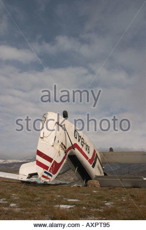 Biplane aircraft crashed by very strong wind, lying inverted with tail high in the air - Stock Image