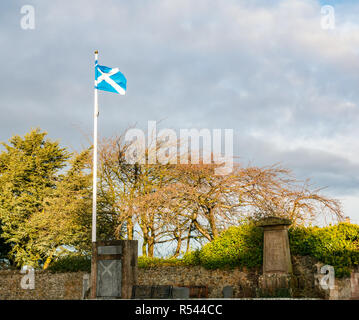 Athelstaneford, East Lothian, Scotland, United Kingdom, 29th November 2018. Birthplace of St Andrew's Cross, the saltire flag. On the eve of St Andrew's Day at Athelstaneford Parish church yard at the National Flag Heritage Centre with the Scottish National flag blowing in the wind. Legend says that on the eve of a battle between Picts and Angles from Northumbria in 832AD Saint Andrew had a vision of victory and when the Picts saw a white cross formed by clouds in a blue sky they attributed their victory to his blessing, adopting the cross as a flag - Stock Image