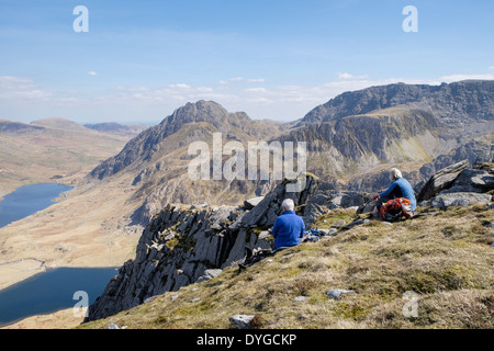 Hikers resting on Y Garn mountain with view to Mount Tryfan and Glyderau in mountains of Snowdonia National Park, Ogwen, North Wales, UK - Stock Image