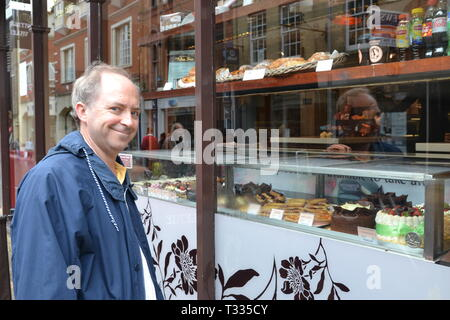 Man looking into cake shop window with a smile, in Ipswich, Suffolk, UK - Stock Image
