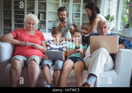 Multi-generation family using laptop, mobile phone and digital tablet - Stock Image