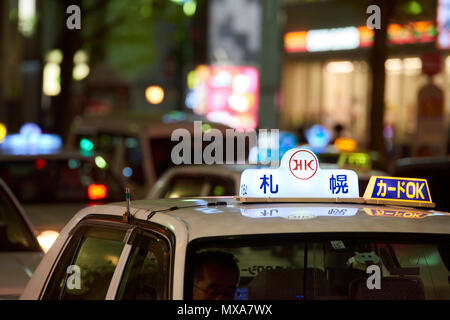 Detail of bright taxi sign at night in Susukino region of Sapporo, Hokkaido, Japan. - Stock Image