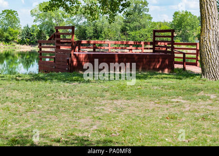 A lookout or fishing dock overlooking a pond in Kansas, USA in the summertime. - Stock Image