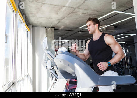 Side view portrait of young adult man in sportswear running on treadmill at gym. Handsome masculinity male training on treadmill and looking to window - Stock Image
