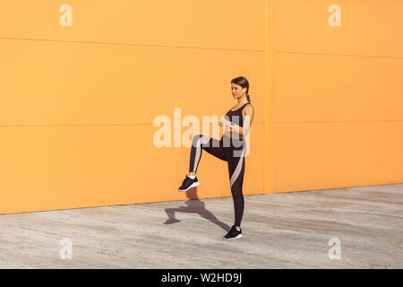 Young attractive sporty woman wearing black sporwear practicing sport exercises in morning on street, standing with raised leg and holding balance, or - Stock Image