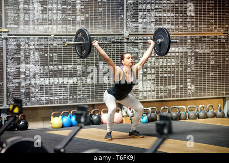 Young woman performing the snatch in a gym lifting a barbell weight from the floor to above her head with extended arms in a single movement - Stock Image