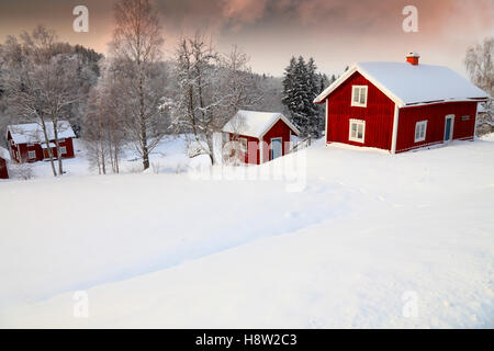 old cottages surrounded by a snowy winter scenery in rural Sweden - Stock Image