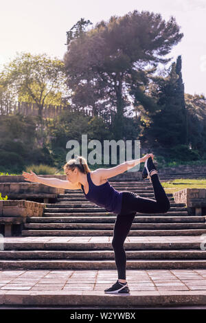 beautiful young woman doing yoga balance exercise on the stairs of the park, morning workout outdoors, sports and healthy lifestyle - Stock Image