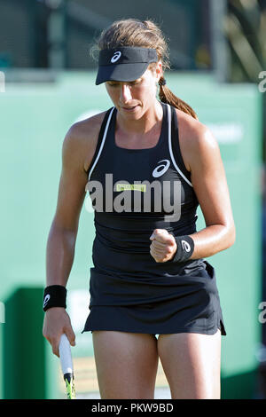 British professional tennis player Johanna Konta (Jo Konta) pumps her fist after winning a point during a singles match. Konta is wearing Asics branded tenniswear and is sponsored by Nature Valley. At the time of the photograph Konta was the British #1 woman in the WTA rankings, having recently reached #4 in the world. Konta was born in 1991 in Australia and switched her allegiance to the United Kingdom in 2012. - Stock Image