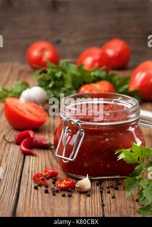tomato sauce in a glass jar, fresh tomato, parsley and spices on a wooden background - Stock Image