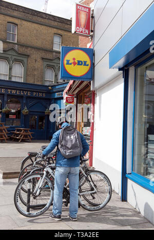 Man with bicycle outside Lidl supermarket in Seven Sister Road, Finsbury Park, London Borough of Islington England Britain UK - Stock Image