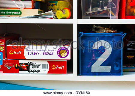 Poznan, Poland - November 18, 2018: Board games and toys laying on book shelves in a toy room. - Stock Image