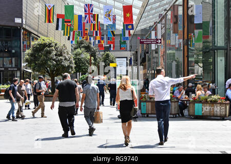 Shoppers walking Westfield Stratford London outdoor shopping centre mall man pointing finger international world flags Newham East London England UK - Stock Image
