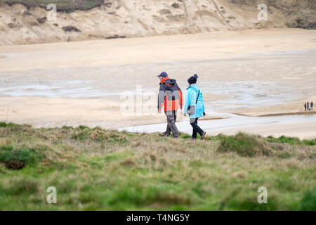 Mature walkers on the coastal path on Pentire Point East in Newquay Cornwall. - Stock Image
