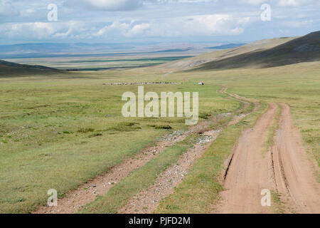 Dirt road leading to a plain in Khövsgól Province, Mongolia, Flock of sheep / goats in the distanve - Stock Image