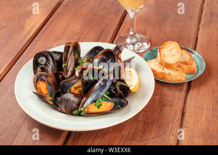 Marinara mussels, moules mariniere, with bread and wine, close-up view on a dark rustic wooden background - Stock Image