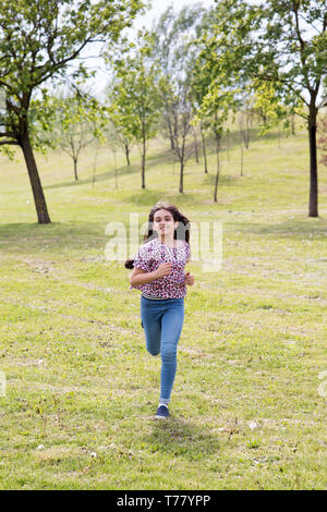 Fit athletic young girl in jeans and sneakers running through a park in spring sunshine with a happy smile approaching the camera - Stock Image