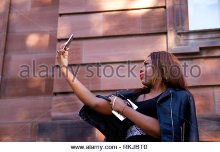 An African female student Nse Udohaya from Nigeria is taking videos of herself on her Apple Iphone outside the Dundee University, UK - Stock Image