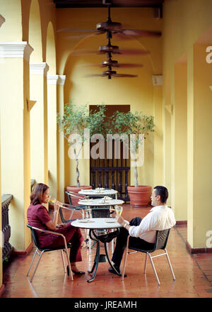 A couple enjoys a glass of wine at the El Picoteo restaurant located inside the El Convento hotel. An architectural landmark in the heart of historic  - Stock Image
