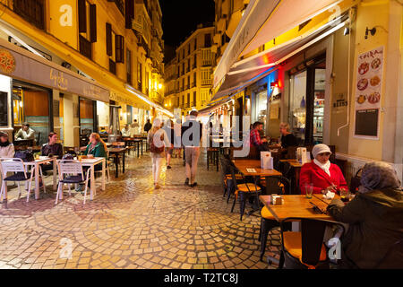 Malaga restaurants - Street with people sitting eating in restaurants cafes and tapas bars at night, Malaga old town, Andalusia Spain - Stock Image