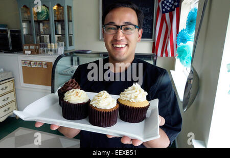 CT- USA David Negreiro owner of Taste and See cupcake shop with some of the shops favorites. - Stock Image