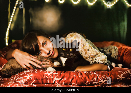 Pretty young woman with her cat laying on a bed with red silk cushions - Stock Image