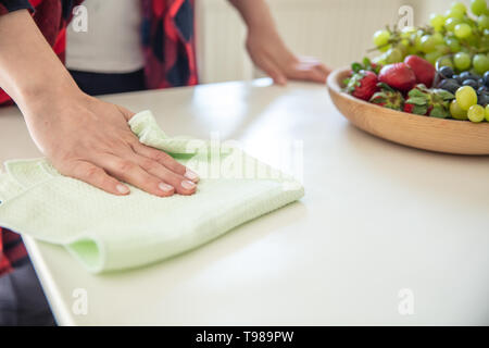 Woman wipes white table with wooden bowl with fruits on it using green cloth. - Stock Image