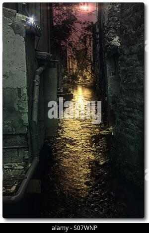Canal with overhead light at night - Stock Image