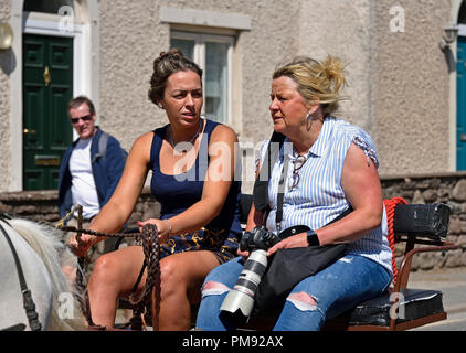 Two Gypsy Travellers riding on trotting cart. Appleby Horse Fair 2018. The Sands, Appleby-in-Westmorland, Cumbria, England, United Kingdom, Europe. - Stock Image