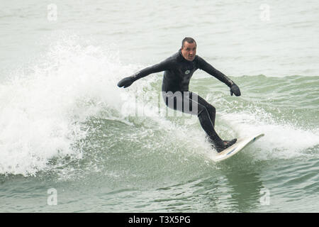 Aberystwyth, Wales, UK. 12 April 2019. UK Weather: Surfers catching the waves at the mouth of the harbour on a fine though overcast April springtime afternoon  in Aberystwyth on the Cardigan Bay coast of west Wales.