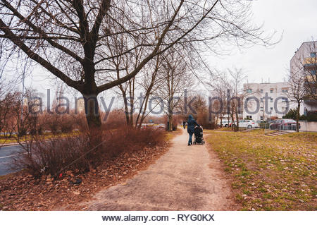 Poznan, Poland - March 3, 2019: Small footpath along a road and green grass with walking people on the Inflancka street. - Stock Image