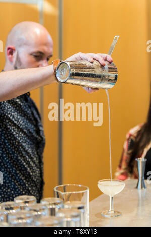 A bartender pouring a cocktail at a pop up bar at Trebah Garden in Cornwall. - Stock Image
