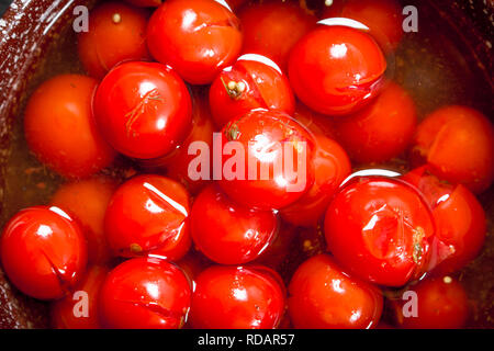 Pickled tomatoes with spices. Top view - Stock Image