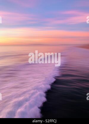 A speed blur of a wave breaking at sunset. Manhattan Beach, California USA. - Stock Image