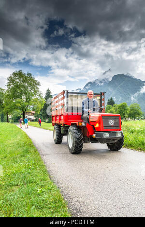 Male Italian farmer using small tractor vehicle for transport. - Stock Image