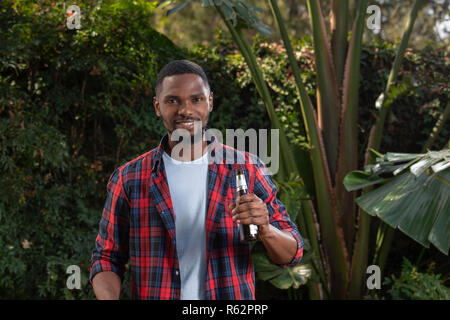 An African man holding a beer in a garden - Stock Image