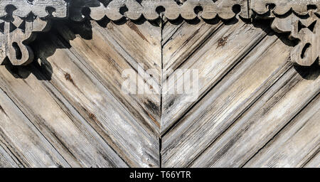 Grunge old weathered wood surface with carvings background - Stock Image