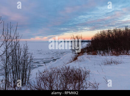 Colorful clouds at sunrise on icy shore of the Lake Superior in winter. Duluth, Minnesota, USA. - Stock Image