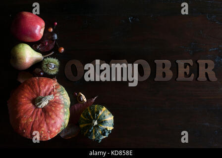 beautiful colorful fall flat lay with leaves, pumpkins, chestnuts and letters october on wooden background - Stock Image