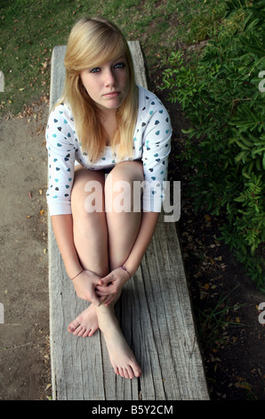 USA A teenager sitting in a park setting - Stock Image