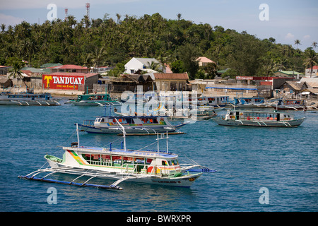 Bangka boats wait off of the Port of Caticlan for their turn to ferry tourists to nearby Boracay Island, Philippines. - Stock Image