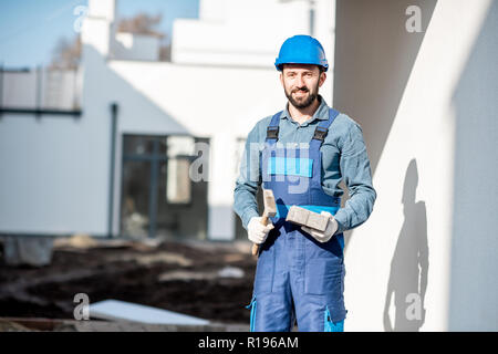 Porait of a builder in uniform holding hummer and paving tile on the construction site with white houses on the background - Stock Image