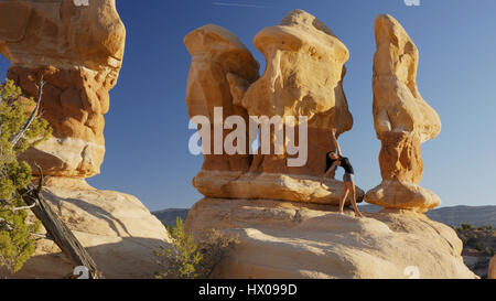 Low angle view of woman dancing and posing on rock formations in remote desert landscape under clear blue sky - Stock Image