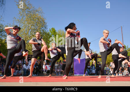 Nis, Serbia - April 20, 2019 People group practicing pose under control of female Piloxing teacher outdoors - Stock Image