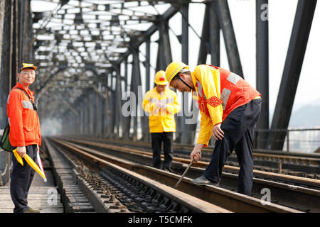 (190423) -- CHONGQING, April 23, 2019 (Xinhua) -- Workers check the previous Baishatuo Yangtze River railway bridge in Jiangjin of southwest China's Chongqing Municipality, April 23, 2019. The previous Baishatuo Yangtze River railway bridge, completed in 1959, will stop service after April 24. All trains will run on the new double decker steel truss cable stay railway bridge after that day. The new bridge has 4 tracks on the upper deck for passenger trains with a designed speed of 200 kilometers per hour and 2 tracks on the lower deck for cargo trains with the designed speed of 120 kilometers  - Stock Image