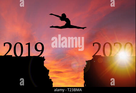 Sunrise silhouette of girl leaping from 2019 toward 2020 over cliff. Concept of boldness, courage, or leap of faith toward a new year. - Stock Image